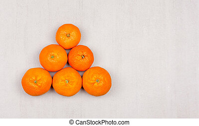pyramid of ripe mandarines on grey background close-up, top view with copy space