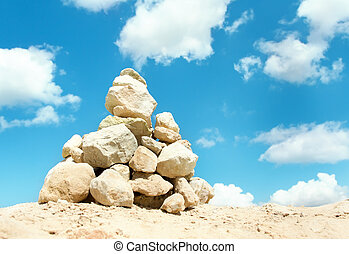 Pyramid of stones stacked outdoors over blue sky background....