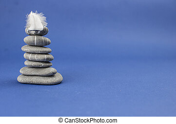 Pyramid of stones with feather on the top. Balance concept