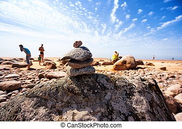 Pyramid of the old stones on the beach with the sun vacationers