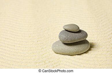 Pyramid of three stones on sand