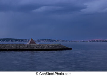 Pyramid on the lake shore at sunset