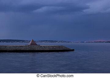 Pyramid on the lake shore at sunset