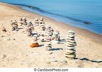 Pyramids of balanced stones on the beach in summer day