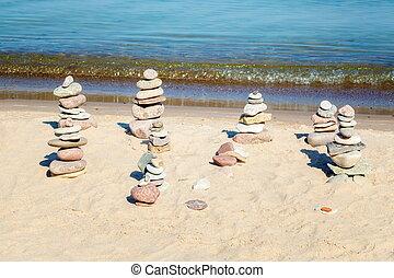 Pyramids of balanced stones on the beach near the sea