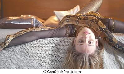 Python crawling on the body of young smiling female dancer...