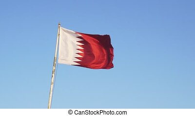 Qatari national flag, with its fields of white and red divided by a jagged line