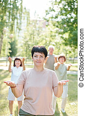 Qigong teacher and her students - Portrait of smiling qigong...