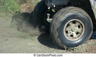 Quad bike driver drifts in the mud. Wheels of quad bike ...