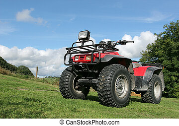 Four wheel drive red and black quad bike standing idle on the grass, with trees and a blue sky with clouds to the rear.