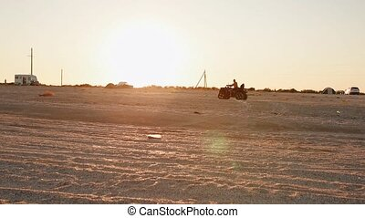 quad biking atv on the sunny beach near sea at sunset