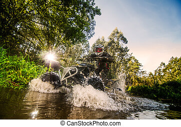 Quad rider through water stream in the forest against ...
