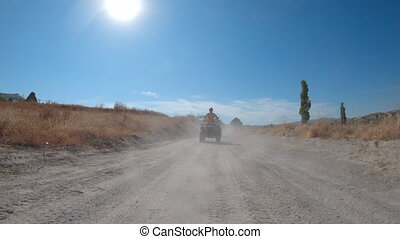 Front view of quadbike driving along dusty road in Cappadocia, Turkey