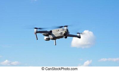 Quadcopter drone against the blue sky. Close up