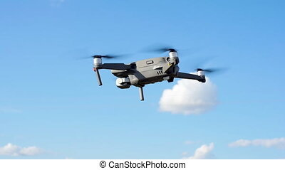 Quadcopter drone against the blue sky. Close up, slow motion