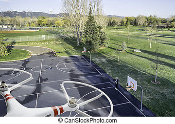quadcopter drone flying over basketball court