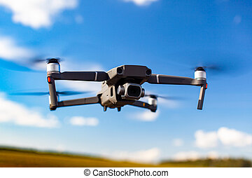 Quadcopter drone flying over blue sea.