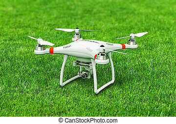 Quadcopter drone with 4K video camera on green grass