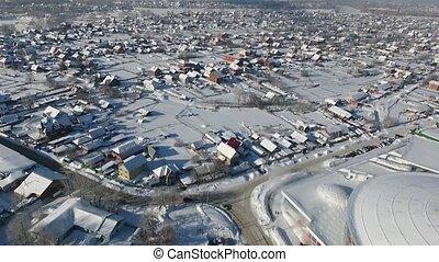 Quadcopter flies over the winter houses. Siberia