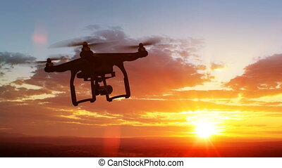 Quadcopter Flying Away to the Beautiful Sunset Scene. Modern...