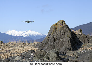 Quadcopter drone flying over rocks on a Southeast Alaskan beach on a sunny day.