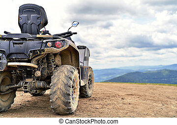 Quadricycle or quad bike on the mountains background