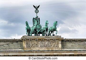 Quadriga on Brandenburg Gate, dramatic cloudy sky background, Berlin, Germany