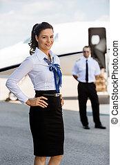 quadril, jato, mãos, contra, terminal, confiante, aeroporto, privado, airhostess, retrato, sorrindo, piloto