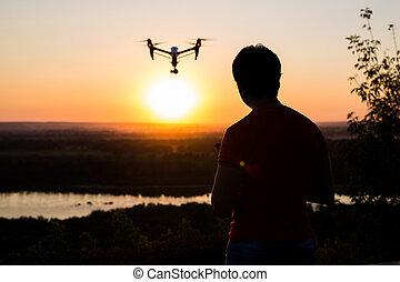 quadrocopter, brummen, mit, entfernt, control., dunkel, silhouette, gegen, colorfull, sunset.