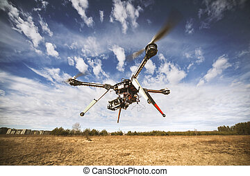 Quadrocopter drone flying in the sky - Flying drone is...