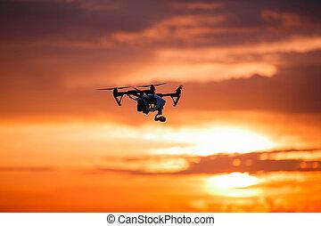 quadrocopter drone with remote control. Dark silhouette...