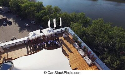 Quadrocopter fly over restaurant with white tent on roof of old building at river. People at wedding
