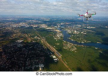 Quadrocopter flying over farmland