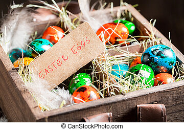 Quail and hen eggs for Easter in old wooden box