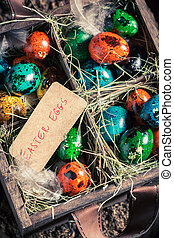 Quail and hen eggs for Easter in wooden box