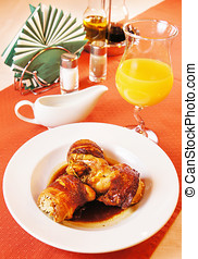 Quail carcasses stuffed with rice on a laid table