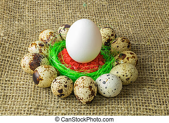 quail eggs and chicken egg with are in a circle around the plastic blue bowl of red salt on a wooden table