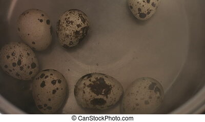 Quail eggs cooking on a boiled water inside of an stainless steel pan on a gas hob .
