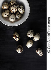 Quail eggs. Flat lay composition with small quail eggs in the bowl on the black wooden background.