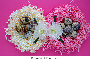 Quail eggs in a decorative nest on a pink background. The concept of Easter celebration.