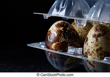 Quail eggs in a plastic container on a dark wooden background, top view, selective focus, shallow depth of field