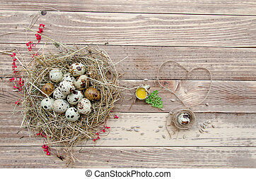 Quail eggs in a straw nest on the old wooden table background. Retro vintage style.