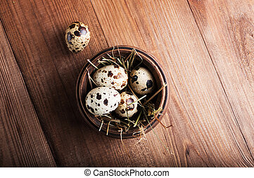 Quail eggs in a wooden bowl on the table