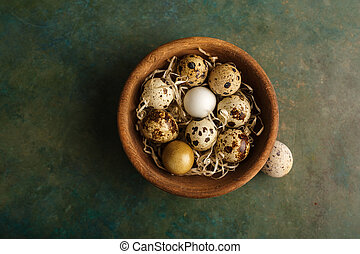 Quail eggs in a wooden bowl.