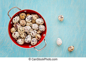 Quail eggs in red collander on a blue wooden background, top view