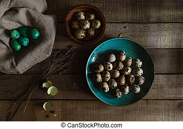 Quail eggs in teal colored plate, colored eggs, emply egg shells on wooden rustic background. Easter scene