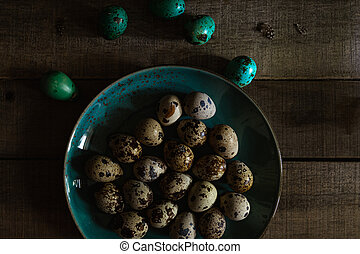 Quail eggs in teal colored plate, colored eggs on wooden rustic background, closeup view