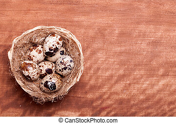 quail eggs in the nest of a view from the top of the wooden background