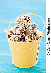 Quail eggs in yellow metal bucket, on blue wooden background