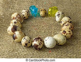 quail eggs lying around along with a small glass blue and yellow elephants on a wooden table with natural burlap